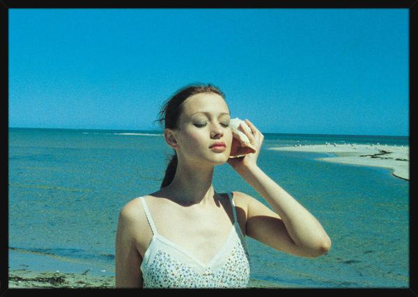 En kvinne på en strand med en konkylie, av kunstner Aune Sand. Poster i en svart ramme.