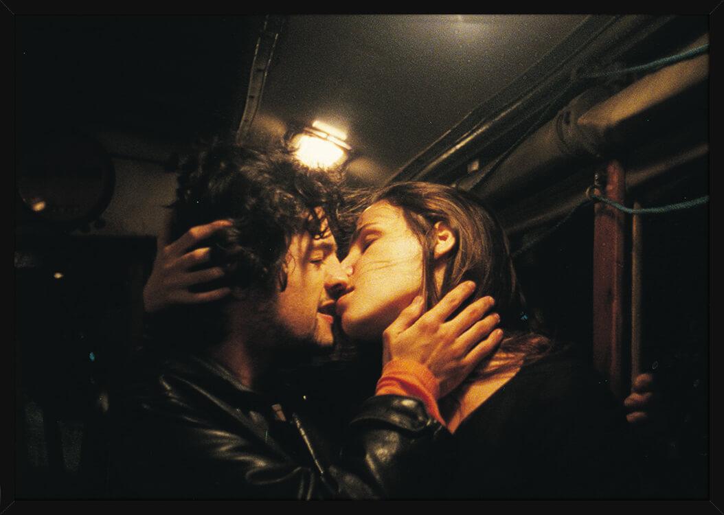 Et kyssende kjærlighetspar, av kunstner Aune Sand. Poster i en svart ramme.