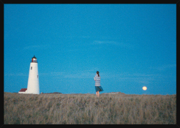 A woman stands in a field between a lighthouse and the moon, filmed by Aune Sand. Print of a photograph in a black frame.