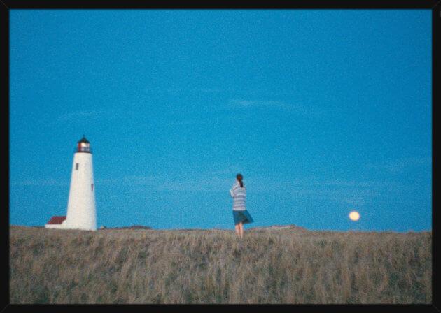 Romantisk landskap med en kvinne, fyr og måne under en blå himmel, av kunstneren Aune Sand. Poster i en hvit ramme.
