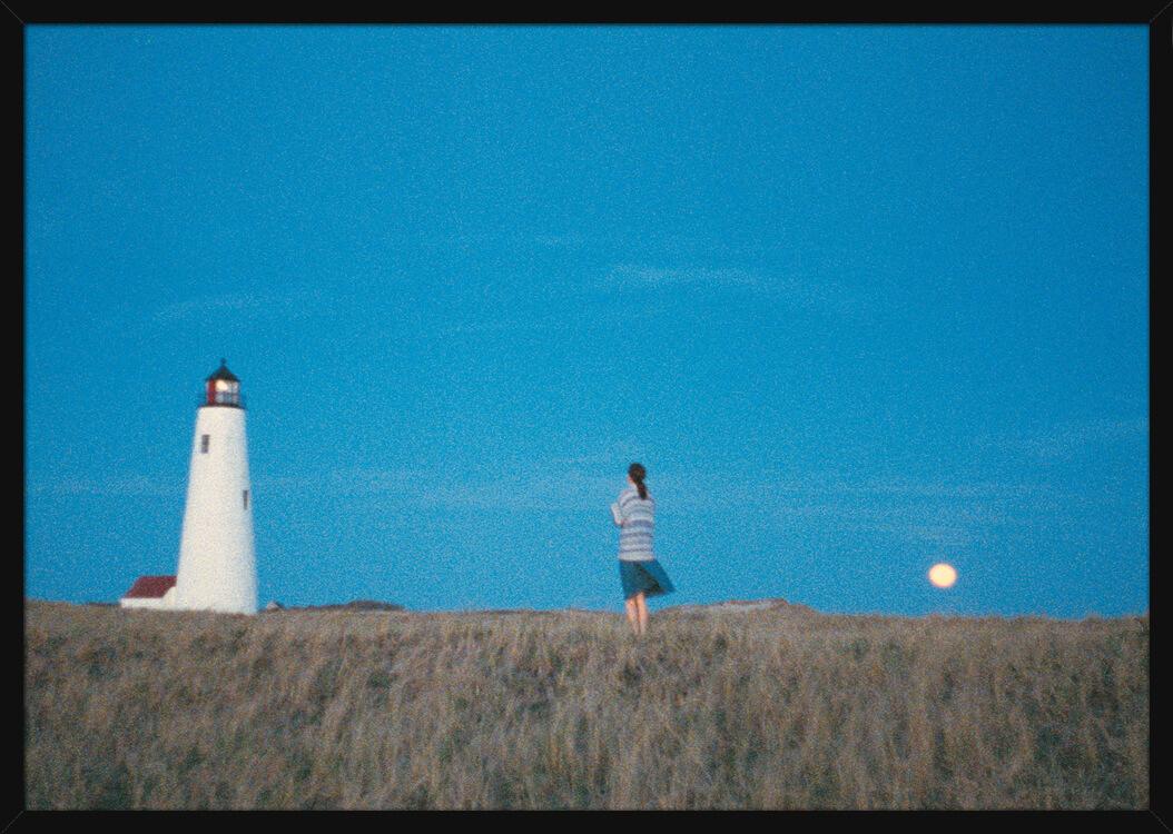 En kvinne står i et landskap mellom et fyr og månen, av kunstner Aune Sand. Poster i en svart ramme.