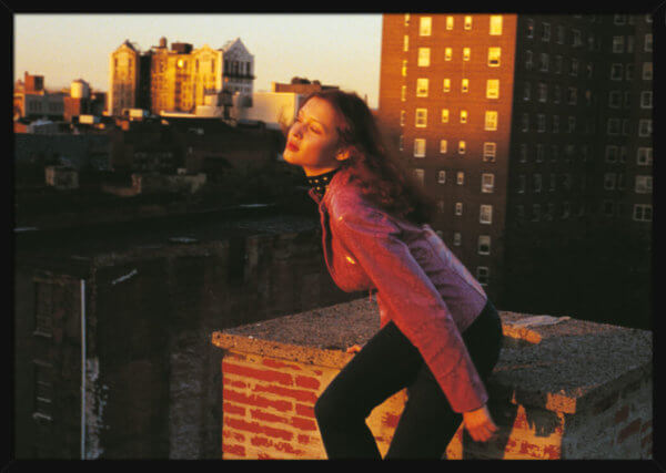 A woman on a rooftop during sunset, filmed by Aune Sand. Print of a photograph in a black frame.
