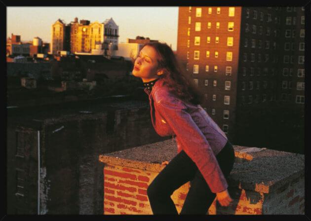 Kvinne på en tak under solnedgang i Harlem, New York City, av den norske artisten Aune Sand. Poster i en hvit ramme.