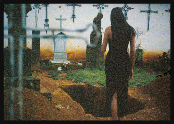 A woman in a dark dress visits a cemetery, filmed by Aune Sand. Print of a photograph in a black frame.