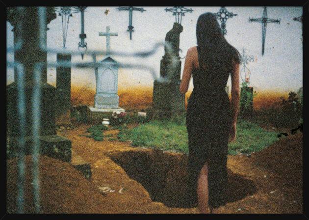 En kvinne i en svart kjole står på en kirkegård, av den norske artisten Aune Sand. Poster i en hvit ramme.