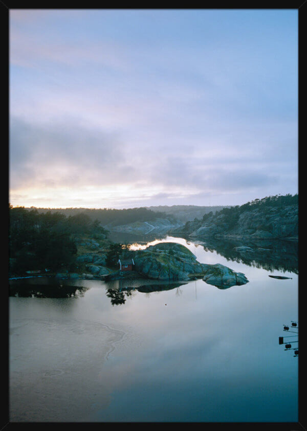 A calm river during sunrise, photographed by Haakon Sand. Art print in a black frame.